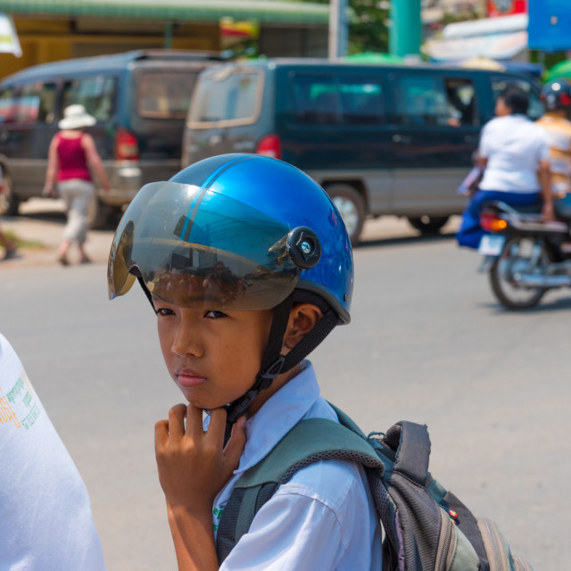 """Young Boy Riding on the Back of a Motorcycle in Cambodia"" stock image"