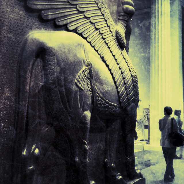 """""""A woman explores a gallery of the British Museum in London, with a colossal Assyrian statue of a winged lion from the palace entrance of king Ashurnasirpal towering over her."""" stock image"""