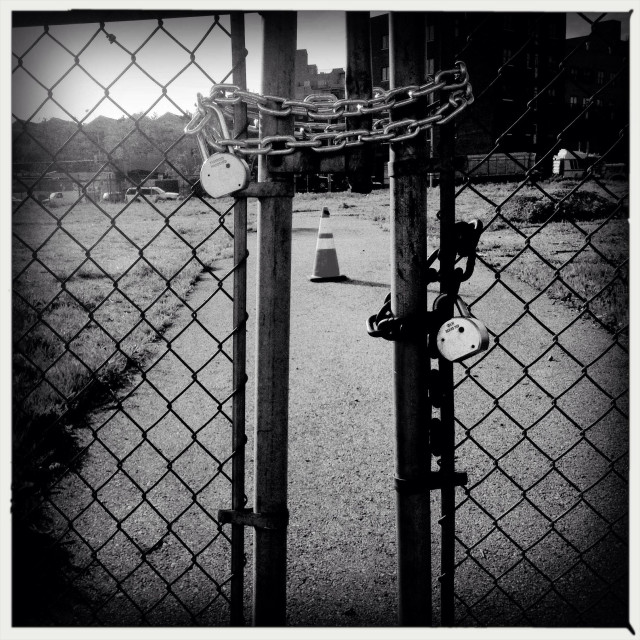 """""""Closed fence at one of the last empty lots in south Williamsburg, the land belongs to Pfizer, but the company moved out their plant in Flashing Ave and Marcy Ave in 2010"""" stock image"""