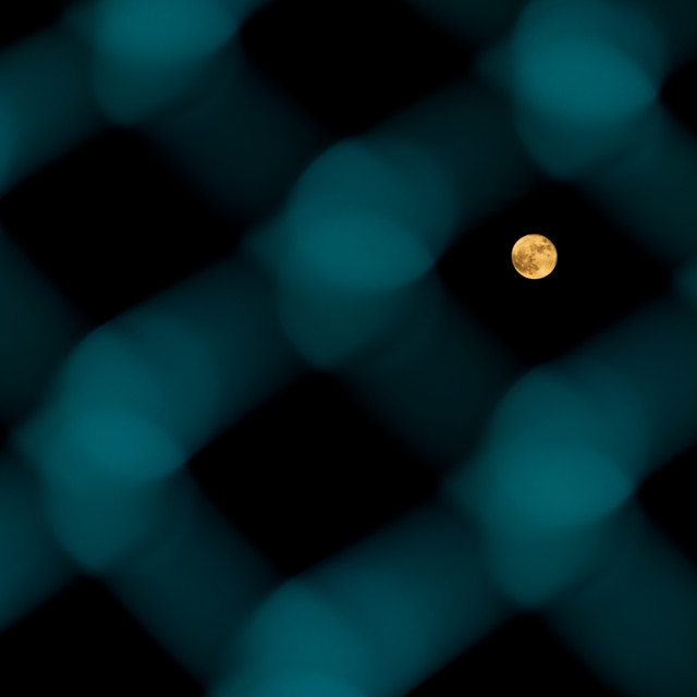 """Moon through the fence"" stock image"