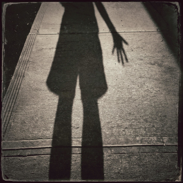 """Shadow of a man in shorts on a sidewalk."" stock image"