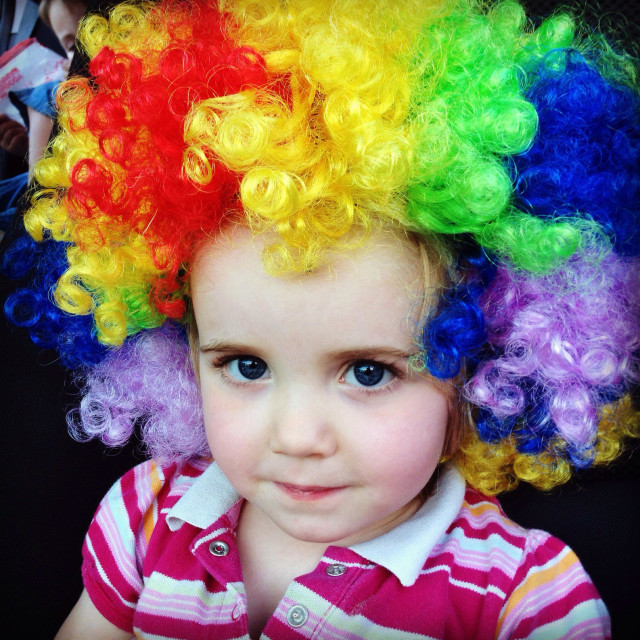 """Little girl with rainbow clown wig"" stock image"