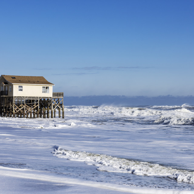 """Beach house on stilts surrounded by high tide surf, Nags Head, Outer Banks, North Carolina, USA"" stock image"