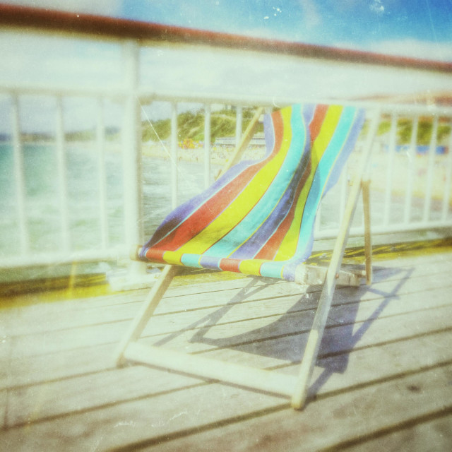 """Brightly coloured script deck chair on a wooden seaside pier"" stock image"