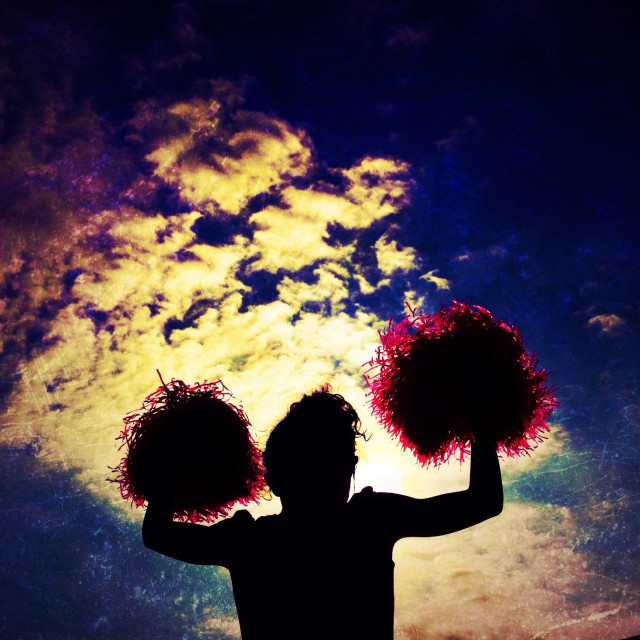 """Cheerleader waving Pom poms against dramatic sky"" stock image"