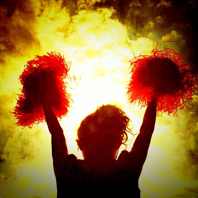 """""""Cheerleader in silhouette against dramatic background"""" stock image"""