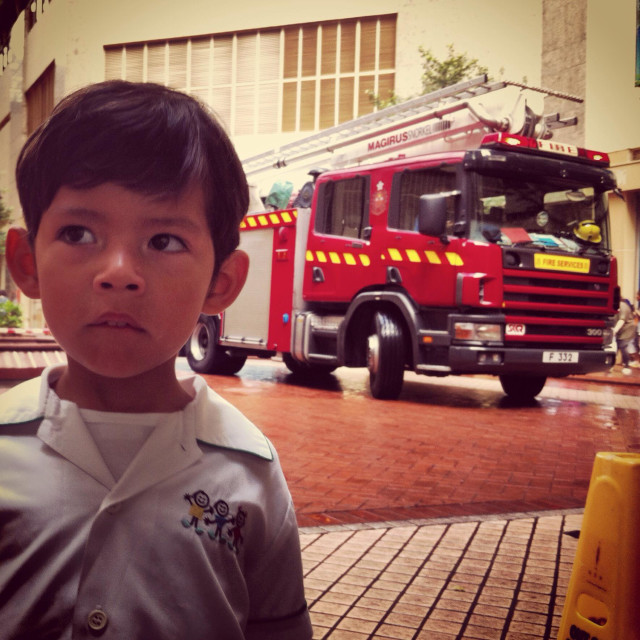 """It's a photo of a child who is worry because of the firemen intervention with their firetruck"" stock image"