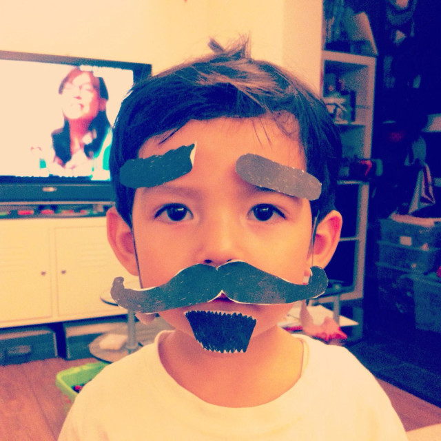 """It's a photo of a young child who pretends to be an adult by wearing a fake paper mustach and paper eyebrows. It's a funny cute boy"" stock image"