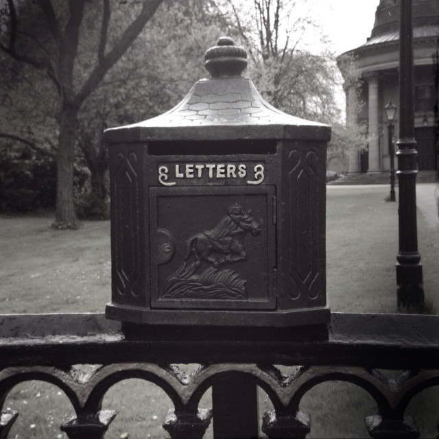"""""""Old fashioned letterbox on an iron fence."""" stock image"""