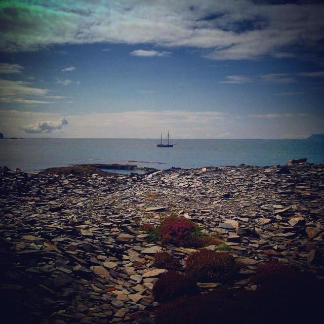 """Lone boat sailing on Scotland's West coast taken from slate shoreline Easdale Island"" stock image"