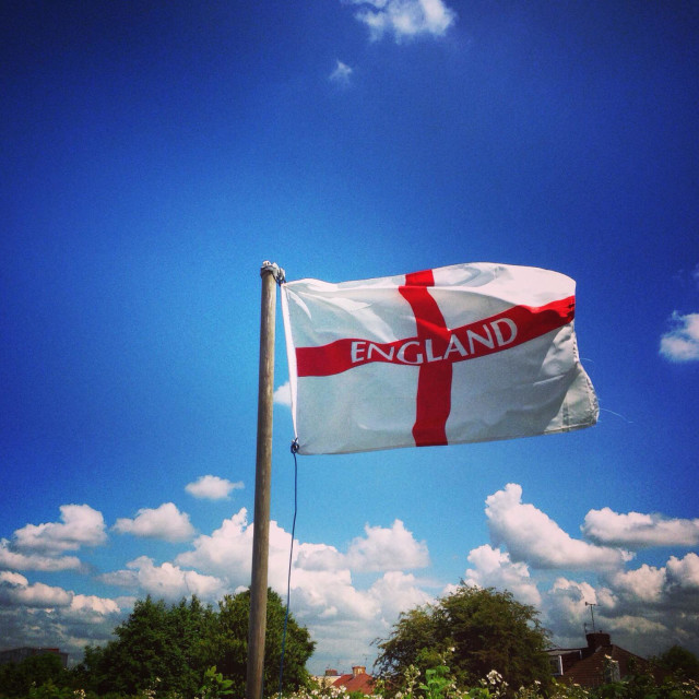 """""""England Flag of St George flying against a blue sky"""" stock image"""
