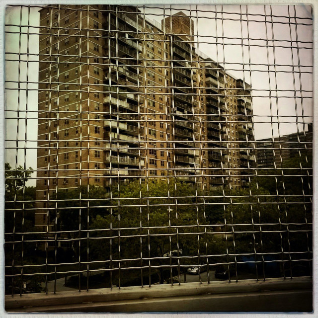 """""""Project building in Bushwick, Brooklyn see through the net fence at the Lorimer Street subway station."""" stock image"""