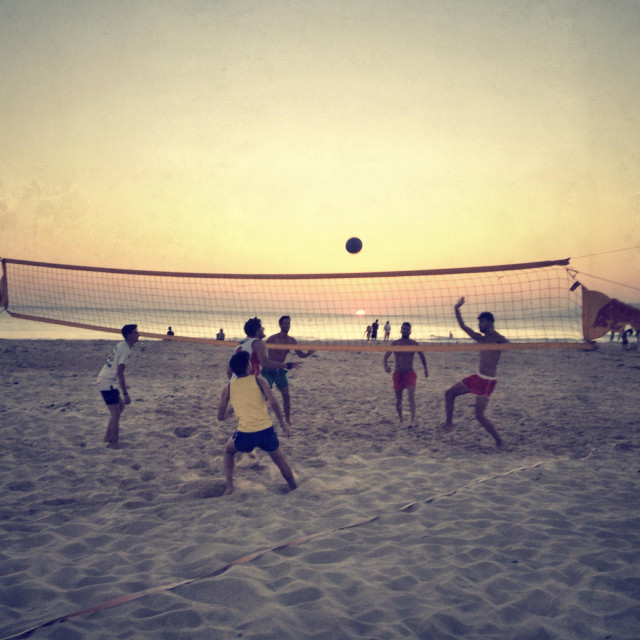 """People on the beach playing volley ball at sunset."" stock image"