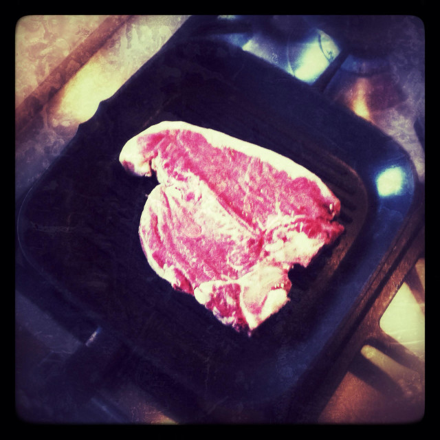 """T-bone steak cooking on a griddle pan"" stock image"