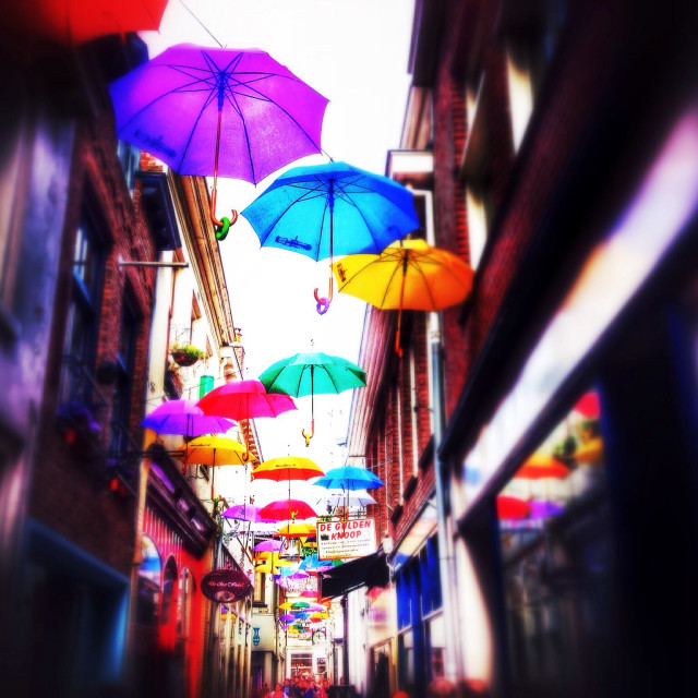 """""""Colorful umbrellas floating above a small shopping street"""" stock image"""