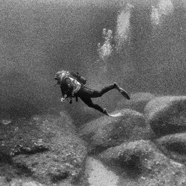 """Young female scuba diver swimming over limestone rocks at depth"" stock image"