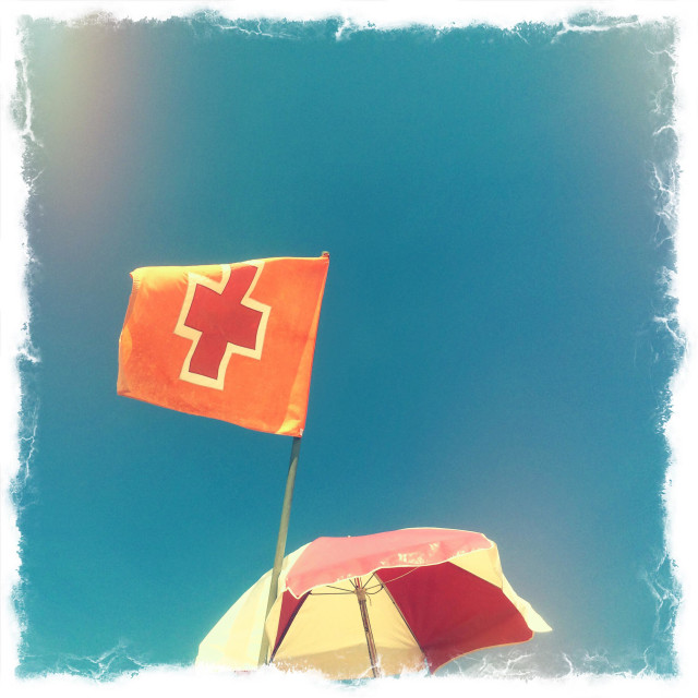 """A Red Cross flag and an umbrella for shade over a lifeguard's chair at the beach, Jacksonville Beach, Florida, USA."" stock image"