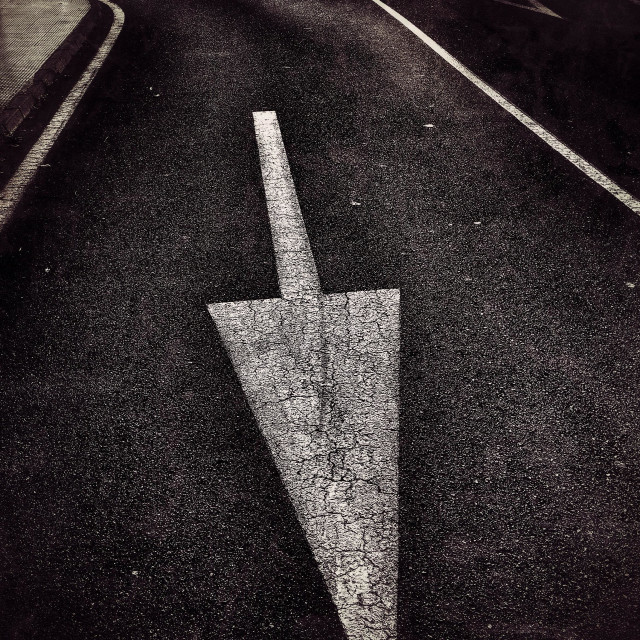 """""""Direction arrow on road with pedestrian crossing in background"""" stock image"""