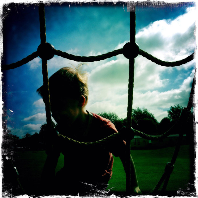 """Boy climbing a rope net climbing frame"" stock image"