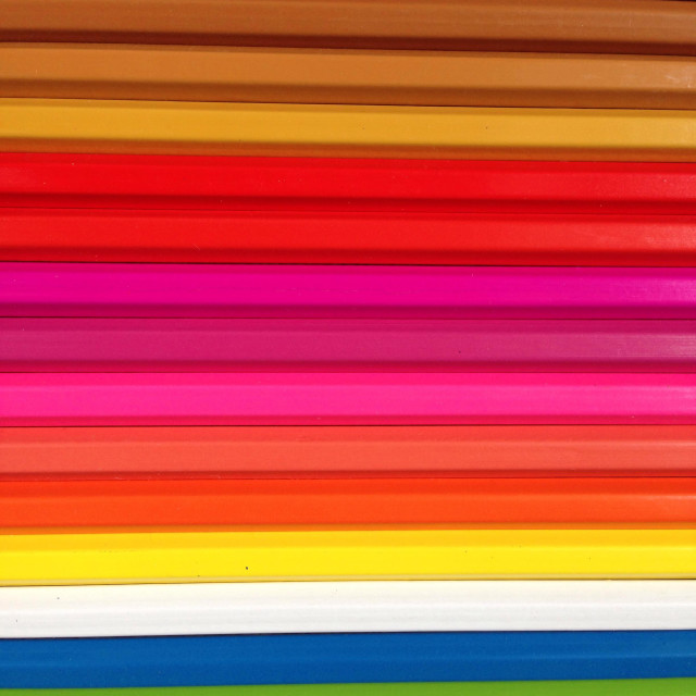 """Coloured pencils lined up to make colourful stripes."" stock image"