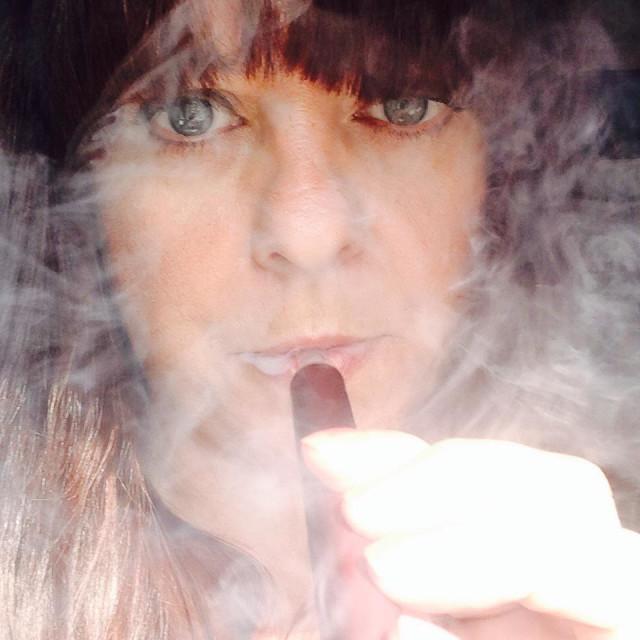 """Woman smoking an E cigarette shisha pen. (Selfie)"" stock image"