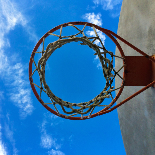 """""""Playground basketball hoop and backboard against a blue sky"""" stock image"""