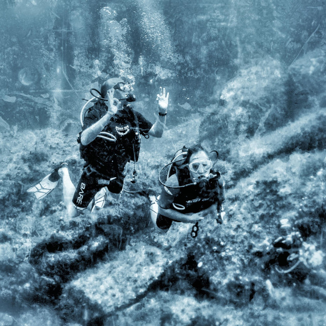 """Two new scuba divers on deep adventure dive bring watched by dive master"" stock image"
