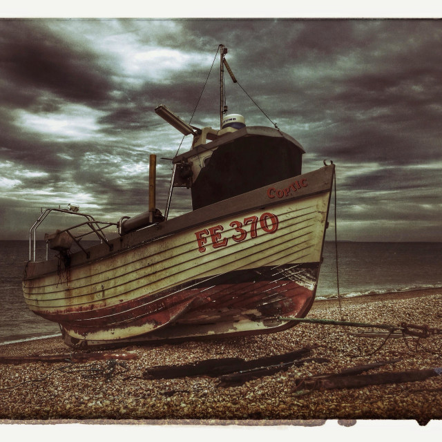 """""""Fishing Vessel on Shingle Beach in Kent, England. Dark storm clouds are rapidly moving over a calm sea. Photo Credit - © COLIN HOSKINS."""" stock image"""