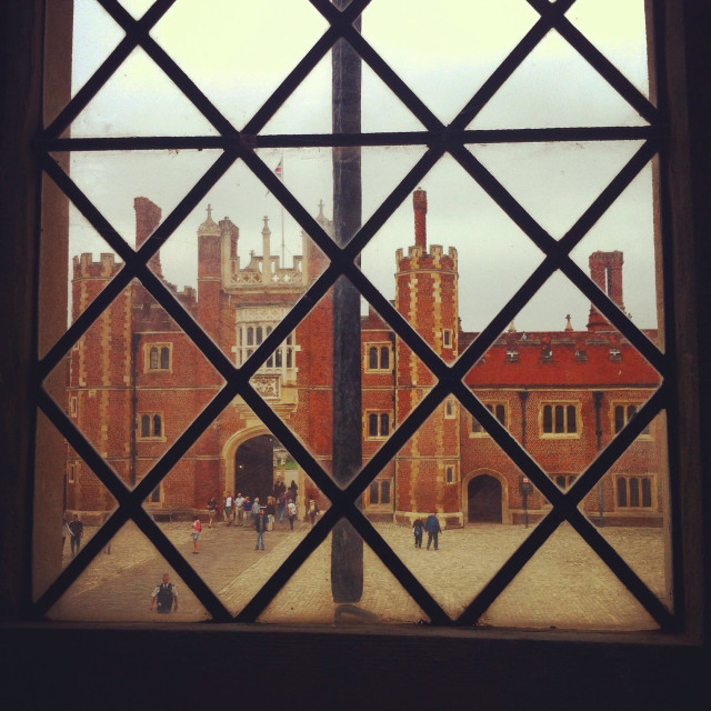 """""""View of base court through a leaded window at Hampton Court Palace, Surrey"""" stock image"""