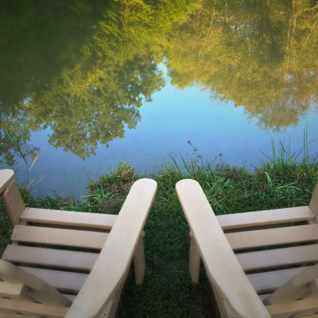 """""""Chairs by a pond with reflection of trees and sky"""" stock image"""