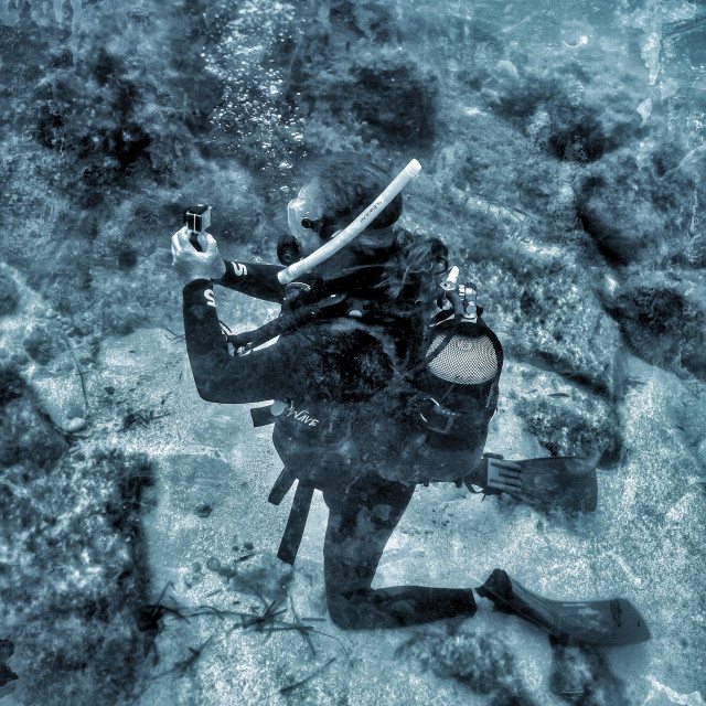 """""""Mature male scuba diver filming his partner underwater with a GoPro camera."""" stock image"""
