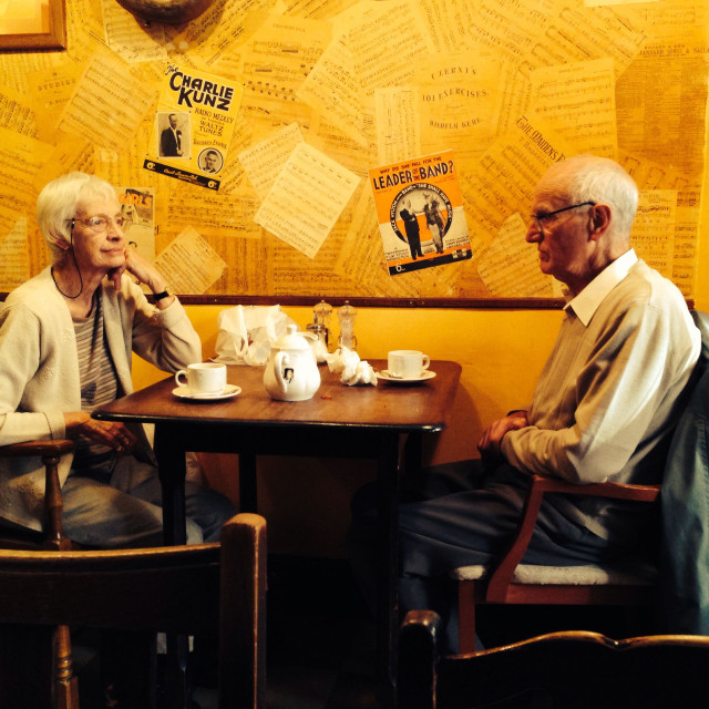 """""""Older couple sitting at table in cafe"""" stock image"""