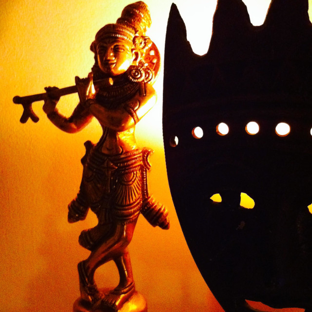 """""""Gold statue and eerie Mexican face against golden glowing light"""" stock image"""
