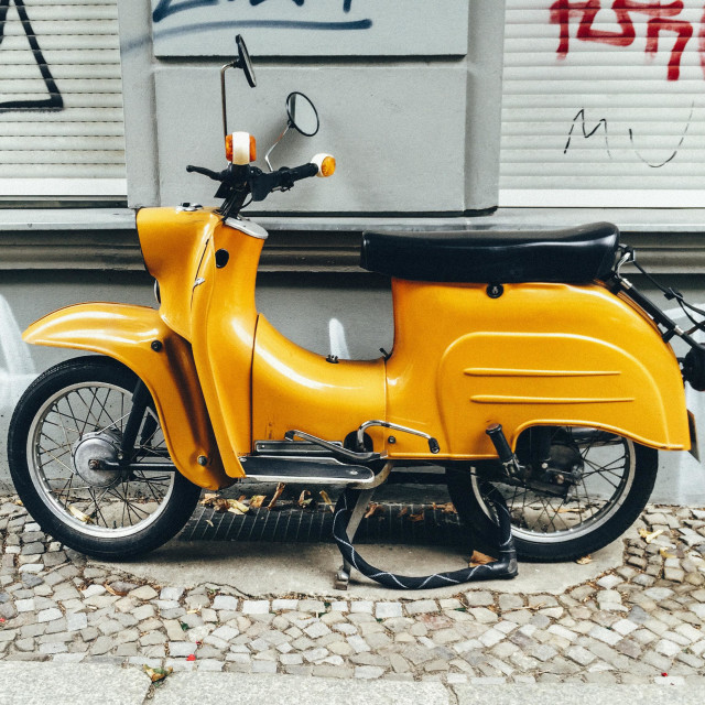 """""""Old yellow motor scooter parked on berlin street in front of graffitied wall"""" stock image"""