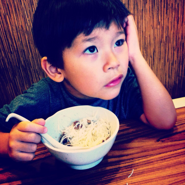 """Little handsome chinese boy is not eating his noodle soup"" stock image"