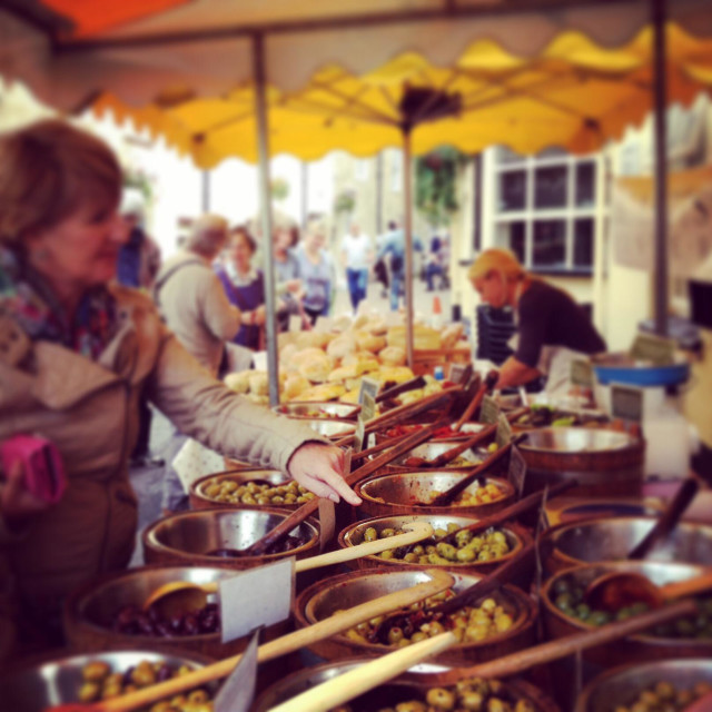 """Choosing olives on a market stall at Stroud farmers market, Gloucestershire, UK"" stock image"