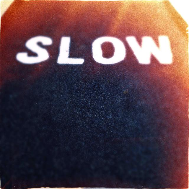 """""""Slow sign painted on cycle path to warn cyclists of pedestrians"""" stock image"""
