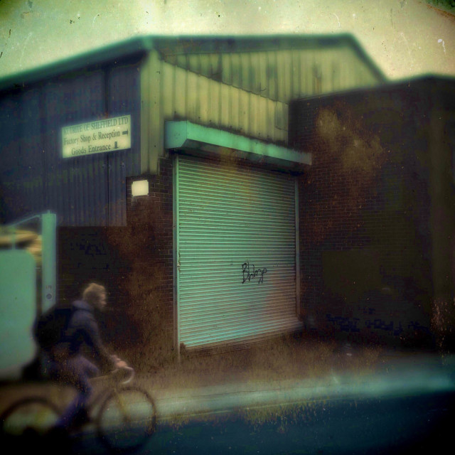 """""""A man in a bike rides past a industrial unit"""" stock image"""
