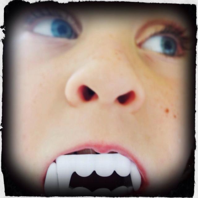 """Little girl with plastic vampire teeth."" stock image"