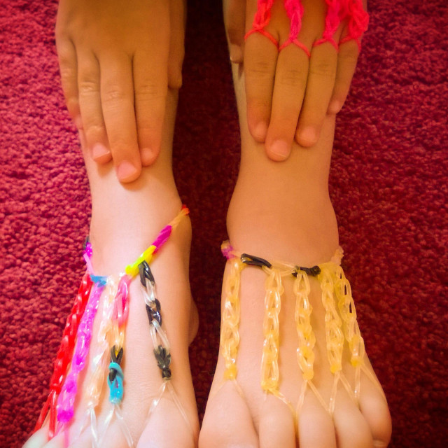 """""""Loom band creations on a Girl's hands and feet."""" stock image"""