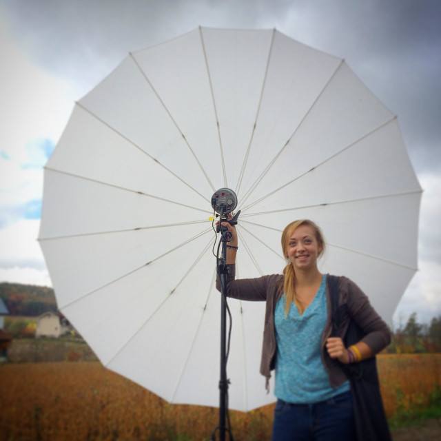 """Photo assistant with large umbrella light"" stock image"