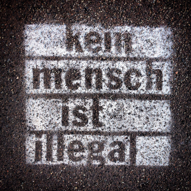 """Spray painted graffiti on sidewalk with words ""Kein Mensch ist illegal"" written in German (No Person is Illegal)"" stock image"