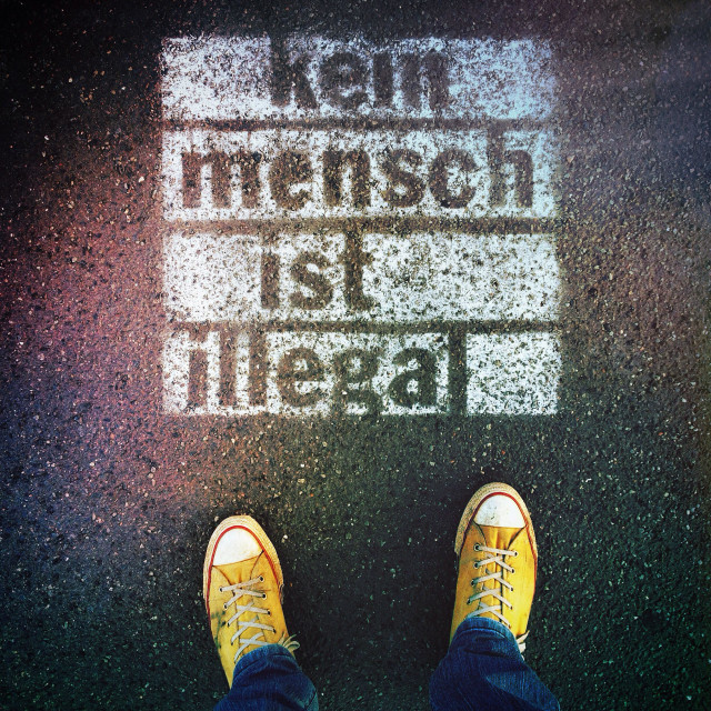 """Person's feet standing next to spray-painted graffiti on sidewalk with words ""Kein Mensch ist illegal"" written in German (No Person is Illegal)"" stock image"