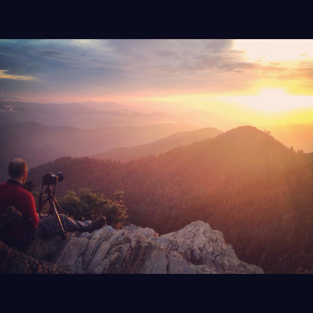 """A photographer sits with his camera and watched a beautiful sunset develop over the smoky mountains"" stock image"