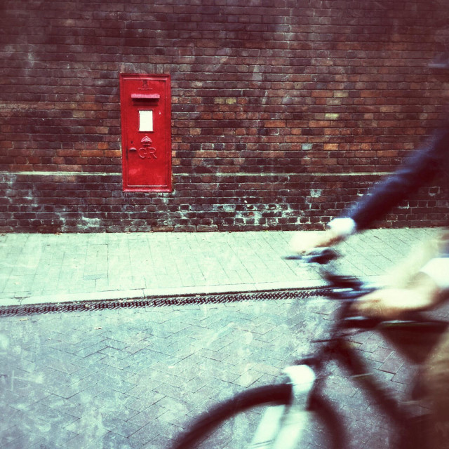 """""""Cycling by a red postbox"""" stock image"""