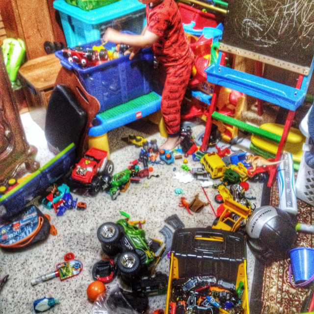 """""""Too many toys! 4 year old boy with his toys scattered all around him."""" stock image"""