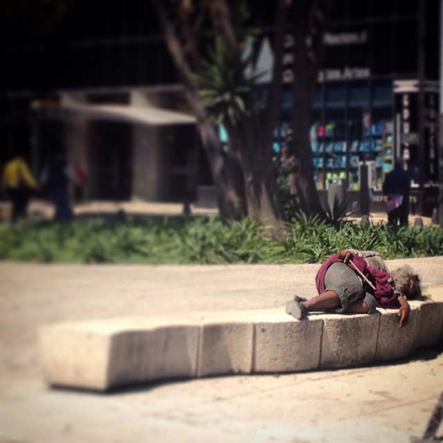 """A homeless sleeps in a bench in Reforma Avenue, Mexico City, Mexico"" stock image"