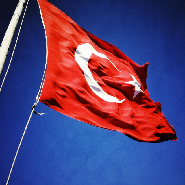 """The Flag of the Republic of Turkey. A red flag with a white 5 pointed star and white Crescent Moon fluttering in a blue sky. Vexillology. Al Bayrak. Al Sancak."" stock image"