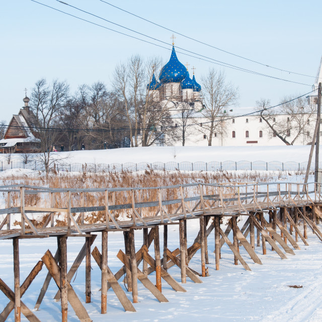 """""""Wooden bridge across the river on the background of the Suzdal Kremlin"""" stock image"""