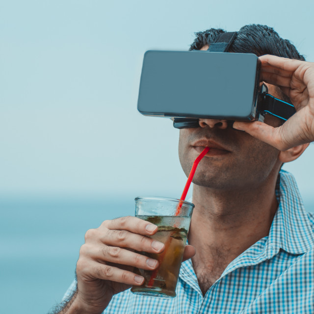 """""""Man with virtual reality goggles mobile device drinking cocktail outdoors on the beach with sea and sky in the background. Concept of online futuristic virtual lifestyle"""" stock image"""